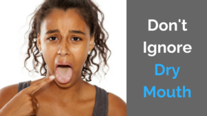 Woman pointing to her open mouth with the caption Don't Ignore Dry Mouth.