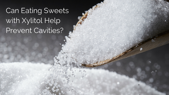 Picture of sugar on a spoon with the words, can eating sweets with xylitol help prevent cavities?