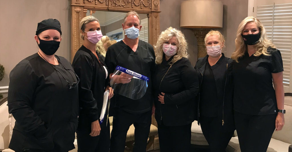 Dr. Lamberton and his team in their Napa dental office posing with PPE ready to serve patients again